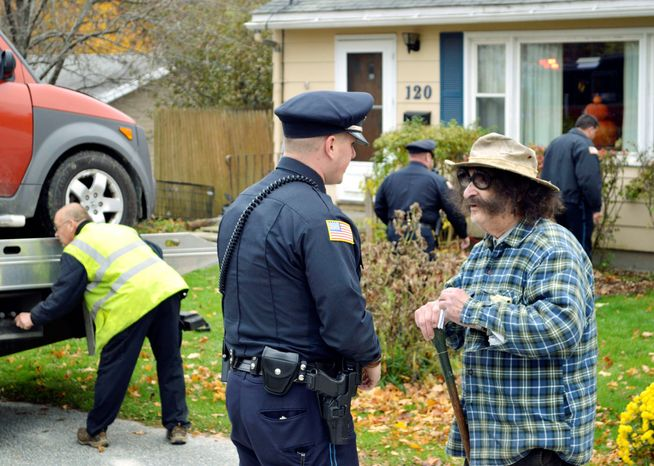 Movie critic Gene Shalit talks with a Lenox, Mass., police officer after crashing his car into a house on Wednesday. Mr. Shalit, 86, faces a misdemeanor charge. (The Berkshire Eagle via Associated Press)