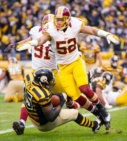 With Redskins linebackers Keenan Robinson (52) and Ryan Kerrigan trailing, Steelers tight end Leonard Pope falls into the end zone for the first score of the game. The touchdown catch on fourth-and-goal from the 1 cappeda 12-play, 76-yard drive during the first quarter. (Andrew Harnik/The Washington Times)