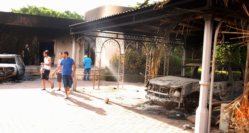 ** FILE ** In this Wednesday, Sept. 12, 2012, file photo, Libyans walk on the grounds of the gutted U.S. consulate in Benghazi, Libya, after an attack the previous day that killed four Americans, including U.S. Ambassador J. Christopher Stevens. (AP Photo/Ibrahim Alaguri)