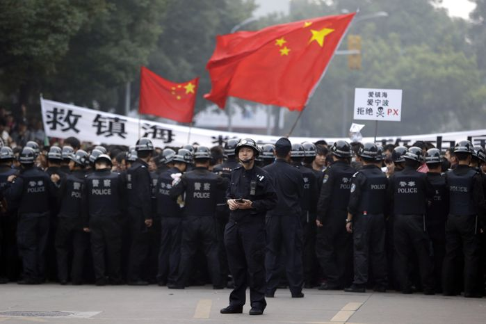 A Chinese policeman stands in front of fellow officers confronting residents who gathered outside the government office in Zhejiang province's Ningbo city on Sunday, Oct. 28, 2012, to protest the proposed expansion of a petrochemical factory. (AP Photo/Ng Han Guan)