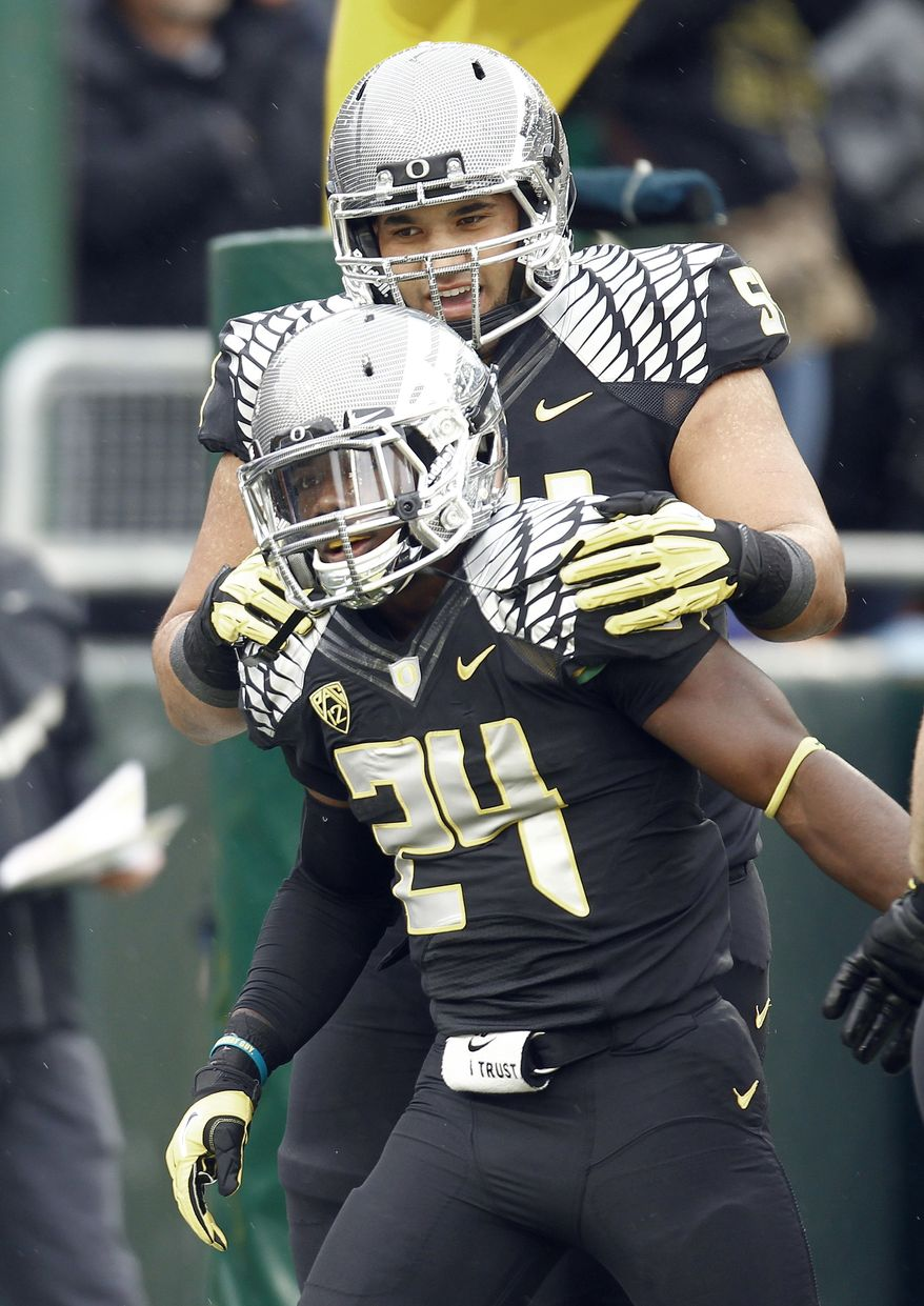 Oregon running back Kenjon Barner, front, celebrates his touchdown with teammate Axel McQuaw during the first half of an NCAA college football game against Colorado in Eugene, Ore., Saturday, Oct. 27, 2012. Barner rushed for 104 yards and two touchdowns, and No. 2 Oregon defeated Colorado 70-14. (AP Photo/Don Ryan)