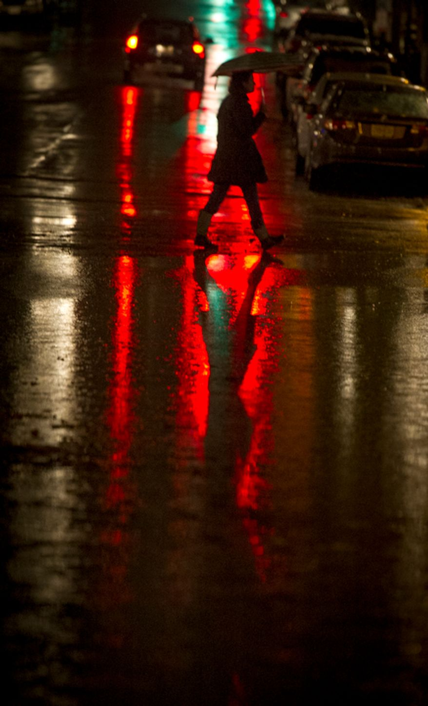 A woman crosses King Street under the shelter of an umbrella in a light rain during high tide, as a little flooding occurs along the waterfront in Old Town Alexandria, Va., Sunday, Oct. 28, 2012 while Hurricane Sandy makes it's way north along the Atlantic coast. (Rod Lamkey Jr./The Washington Times)