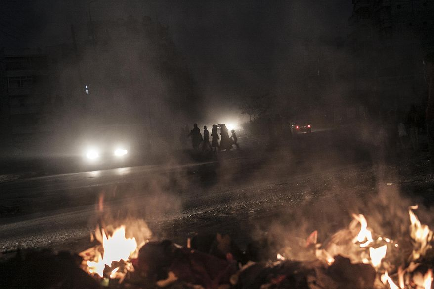 Syrians cross a street as a pile of rubbish burns along the roadside in Aleppo, Syria, on Saturday, Oct. 27, 2012. (AP Photo/Narciso Contreras)