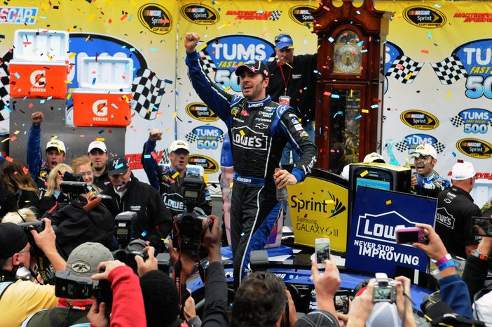 Jimmie Johnson celebrates in Victory Lane after winning the NASCAR Sprint Cup Series auto race at Martinsville Speedway, Sunday, Oct. 28, 2012, in Martinsville, Va. (AP Photo/Don Petersen)