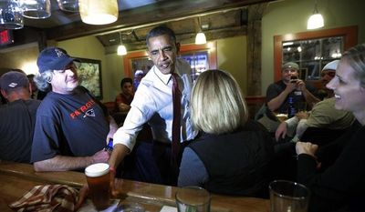 President Obama reaches for his beer on the bar as he greets patrons during an unscheduled visit to the Common Man Merrimack restaurant on Saturday, Oct. 27, 2012, in Merrimack, N.H. (AP Photo/Pablo Martinez Monsivais)