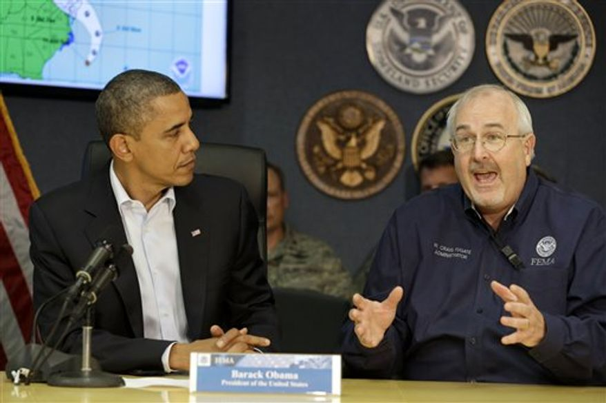 President Obama, left, listens as Federal Emergency Management Agency administrator Craig Fugate speaks to the media at FEMA Headquarters in Washington, on Sunday, Oct. 28, 2012. FEMA is coordinating the deployment of federal resources in preparation for Hurricane Sandy. (AP Photo/Jacquelyn Martin)