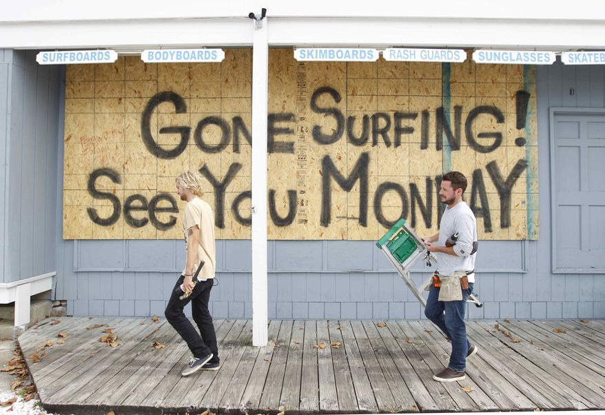 Store workers Fletcher Birch, right, and Jay Kleman finish boarding up the windows on a surf store in Ocean City, Md., on Saturday, Oct. 27, 2012, as Hurricane Sandy approaches the Atlantic coast. (AP Photo/Jose Luis Magana)