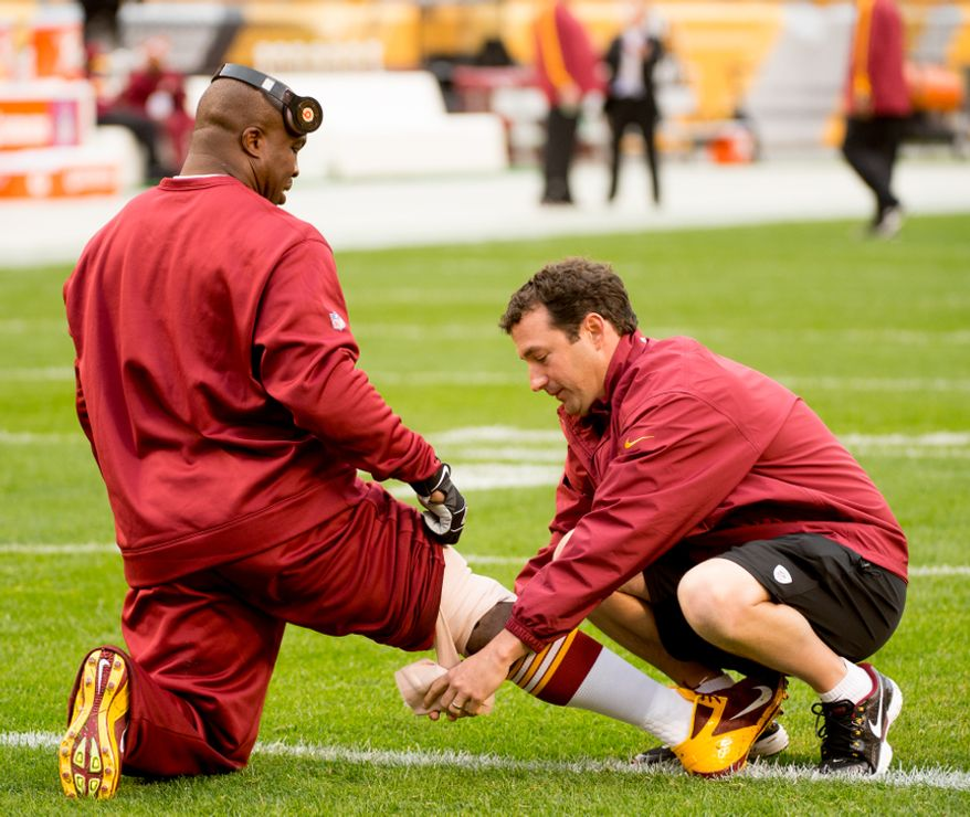 A trainer unwraps the leg of Washington Redskins inside linebacker London Fletcher (59) as he tests the hamstring he injured in last week's game against the New York Giants, as the Redskins warm up before they take on the Pittsburgh Steelers at Heinz Field in Pittsburgh on Sunday, Oct. 28, 2012. (Andrew Harnik/The Washington Times)