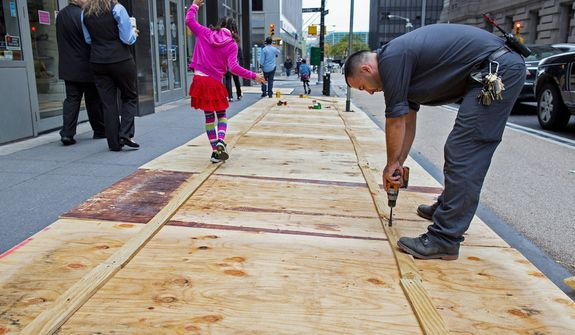 A maintenance worker named Vitto attaches plywood to a sidewalk grate at the 2 Broadway building of Lower Manhattan in New York, Sunday, Oct. 28, 2012, as a child walking by takes advantage of the temporary structure. Areas along the Northeast Coast are preparing for the arrival of Hurricane Sandy and a possible flooding storm surge. (AP Photo/Craig Ruttle)