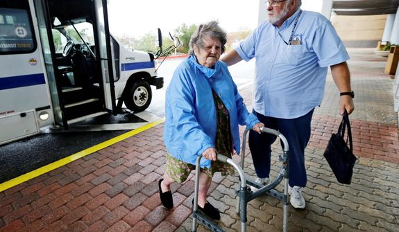 Tom Morehead, a driver with Ocean City, Md., public transportation, assists Evelyn Krainatc to a convention center on her way to a shelter, as Hurricane Sandy bears down on the East Coast, Sunday, Oct. 28, 2012, in Ocean City, Md. Tens of thousands of people were ordered to evacuate coastal areas Sunday as big cities and small towns across the U.S. Northeast braced for the onslaught of a superstorm threatening some 60 million people along the most heavily populated corridor in the nation. (AP Photo/Alex Brandon)