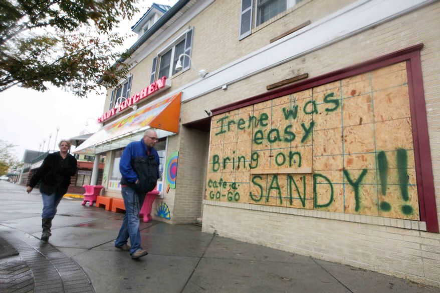 Residents still hang around the Rehoboth boardwalk as businesses board up their windows in preparation for the approaching Hurricane Sandy. (AP Photo/The News Journal, Suchat Pederson)