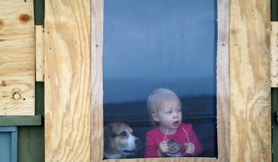 One-year-old Ever Long and her dog, Bailey, peek out the back door of their boarded house for the coming storm as some prepare for the approaching Hurricane Sandy, in Bay View Beach, Del. (AP Photo/The Wilmington News-Journal, Suchat Pederson)