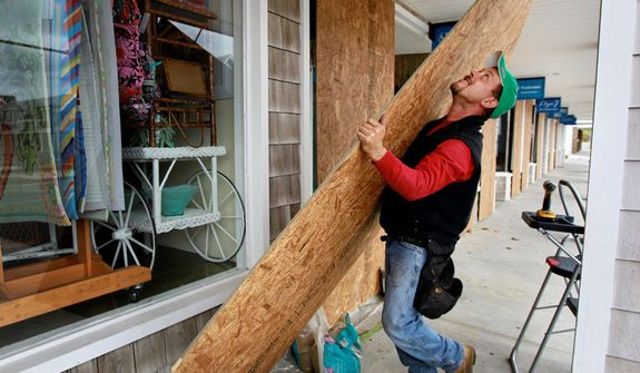 Jeremy Seidel, of Waterford, Conn., covers storefront windows with plywood in the Watch Hill section of Westerly, R.I., Sunday, Oct. 28, 2012, in preparation for high winds from the expected arrival of Hurricane Sandy.  (AP Photo/Steven Senne)