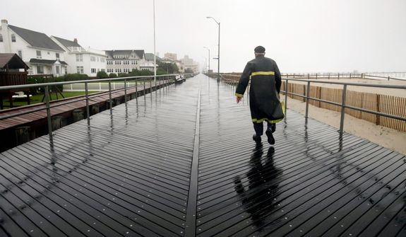 A man walks the boardwalk in Ventnor, N.J., Sunday, Oct. 28, 2012, as the area prepares for Hurricane Sandy.  (AP Photo/ Joseph Kaczmarek)