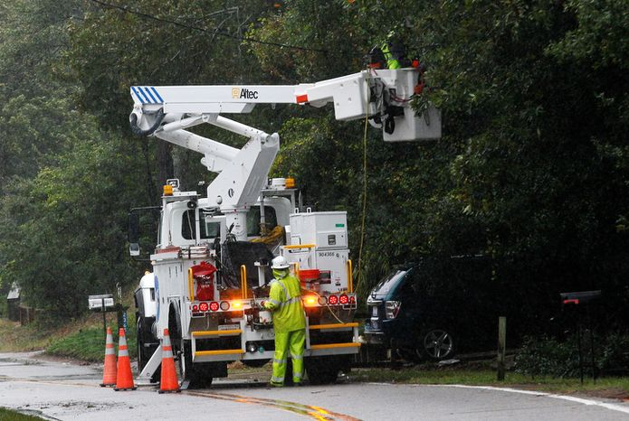 **FILE** Utility workers with Dominion repair damaged lines (AP Photo/Gerry Broome)