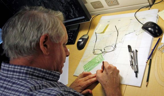 Senior hurricane specialist Stacy Stewart plots NOAA and Air Force aircraft fixes at the National Hurricane Center in Miami, Sunday, Oct. 28, 2012. Hurricane Sandy is heading north from the Caribbean, where it left nearly five dozen dead, to meet a winter storm and a cold front, plus high tides from a full moon, and experts said the rare hybrid storm that results will cause havoc over 800 miles from the East Coast to the Great Lakes. (AP Photo/Alan Diaz)