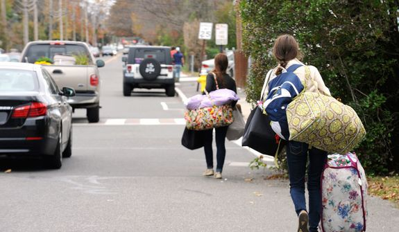 Fairfield University students leave the campus in Fairfield, Conn. Sunday Oct. 28, 2012. Tens of thousands of people were ordered to evacuate coastal areas Sunday as big cities and small towns across the U.S. Northeast braced for the onslaught of a superstorm threatening some 60 million people along the most heavily populated corridor in the nation. (AP Photo/The Connecticut Post, Cathy Zuraw)