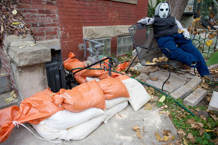 """A stuffed """"Jason"""" replica from the Friday the 13th movies sits on a bench next to a stack of sandbags that line the stairway to a basement apartment in the Bloomingdale neighborhood off of Rhode Island Avenue in Washington, D.C. on Sunday, Oct. 28, 2012. D.C. residents in this neighborhood are particularly concerned about flooding issues from Sandy, the so-called """"Frankenstorm,"""" which is expected to hit the area sometime tonight. (Barbara L. Salisbury/The Washington Times)"""