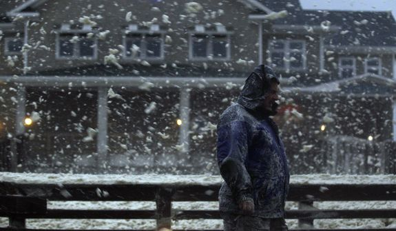 High winds blow sea foam into the air as a pedestrian crosses Jeanette's Pier in Nags Head, N.C., on Sunday, Oct. 28, 2012, as wind and rain from Hurricane Sandy move into the area. (AP Photo/Gerry Broome)