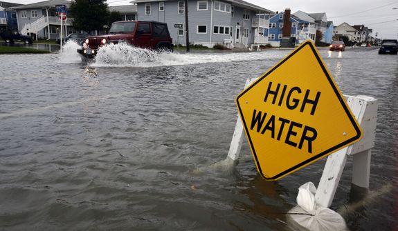 A car goes through high water in Ocean City, Md., on Sunday, Oct. 28, 2012, as Hurricane Sandy bears down on the Mid-Atlantic coast. (AP Photo/Alex Brandon)
