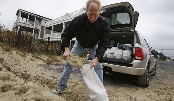Mike Strobel fills sandbags for his business, Mike's Carpet Connection, on Sunday, Oct. 28, 2012, in Fenwick Island, Del., as Hurricane Sandy bears down on the Mid-Atlantic states. (AP Photo/Alex Brandon)