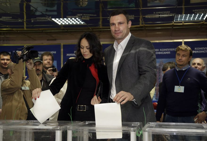 Former boxing champion Vitali Klitschko (center right), chairman of the opposition Ukrainian Democratic Alliance for Reform Party, and his wife, Natalia, cast their ballots at a polling station during parliamentary elections in Kiev on Sunday, Oct. 28, 2012. (AP Photo/Efrem Lukatsky)