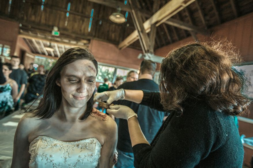 Ronda Drakeford, has make-up applied to her skin as she gets in character to play a zombie at Run for Your Lives, a zombie infested 5k obstacle course run, in Darlington, MD.  (Andrew S. Geraci/The Washington Times)