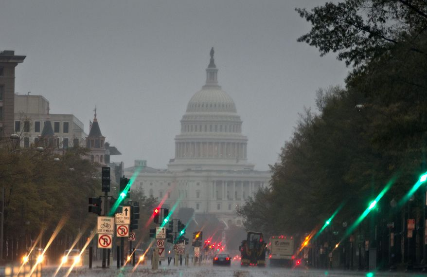 Pennsylvania Avenue is not its usual bumper-to-bumper busy on Monday morning as heavy rain from Hurricane Sandy arrives in Washington. With many hunkered down at home, the commute was easier for those who did venture out. (Associated Press)