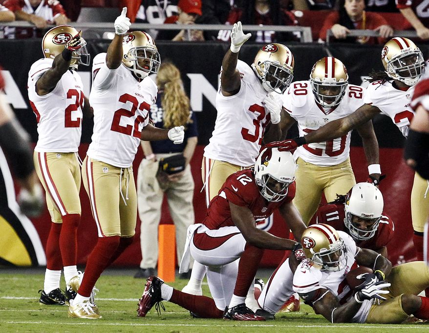The San Francisco 49ers' Chris Culliver (bottom right) intercepts a pass intended for the Arizona Cardinals' Larry Fitzgerald (11) as San Francisco's Tarell Brown (far left), Carlos Rogers (22), Donte Whitner (31), Perrish Cox (20) and Dashon Goldson (far right) and the Cardinals' Andre Roberts (12) all look on during the first half of an NFL football game on Monday, Oct. 29, 2012, in Glendale, Ariz. (AP Photo/Ross D. Franklin)