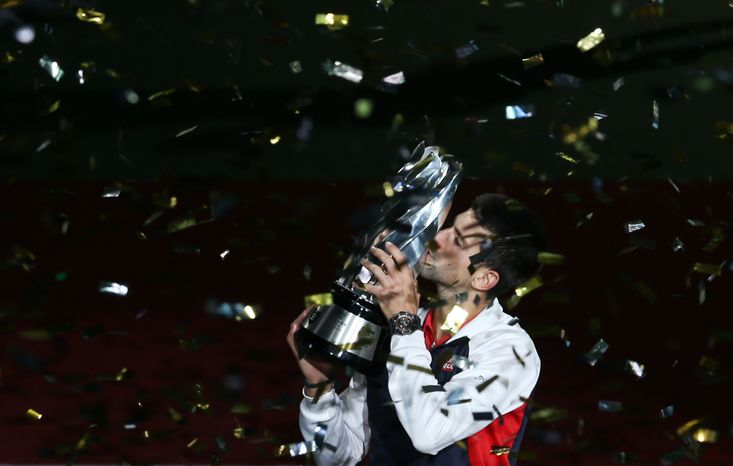 Novak Djokovic of Serbia kisses the trophy after winning the men's singles final match against Andy Murray of Britain at the Shanghai Masters tennis tournament at Qizhong Forest Sports City Tennis Center in Shanghai, China, Sunday Oct. 14, 2012. (AP Photo/Kin Cheung)