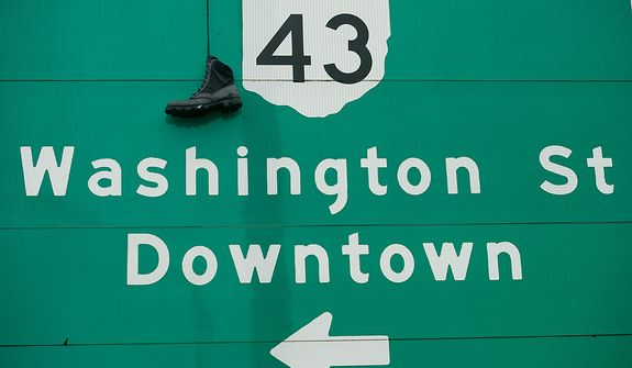 A boot hangs from a highway sign exit for downtown Steubenville, Ohio, Saturday, October 27, 2012. Once a productive steel town, Steubenville, Ohio's population has contracted faster than anywhere else in the country between 1980 and 2000 as their steel plants shut down. The area has seen a drop in unemployment in recent years due in part to the prospects of natural gas but the city still has a long way to go with unemployment figures higher then the the rest of the state and the country. (Andrew Harnik/The Washington Times)