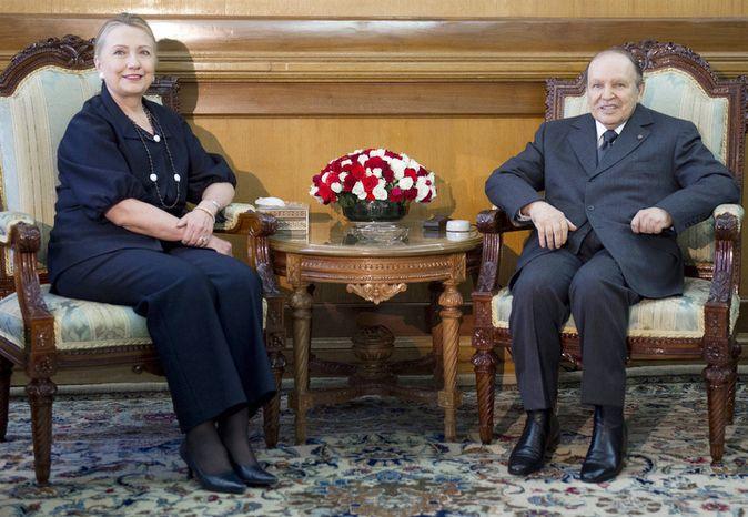 Algerian President Abdelaziz Bouteflika, right poses with photographers with US Secretary of State Hillary Rodham Clinton, at the Mouradia Palace, in Algiers, Algeria, Monday, Oct. 29, 2012. (AP Photo, Saul Loeb, Pool)