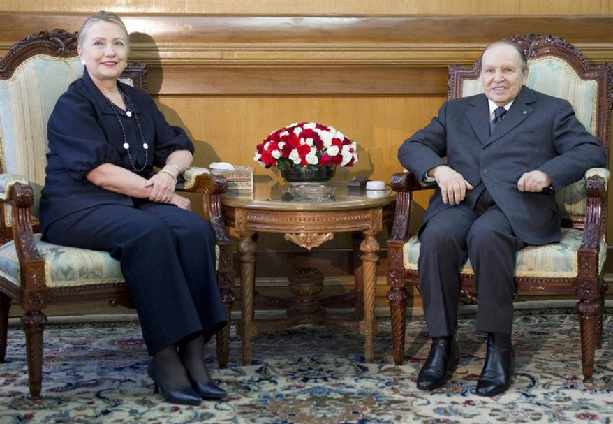 Algerian President Abdelaziz Bouteflika, right poses with photographers with US Secretary of State Hillary Rodham Clinton, at the Mouradia Palace, in Algiers, Algeria, Monday, Oct. 29, 2012. (AP Photo, Saul Loeb, Pool)