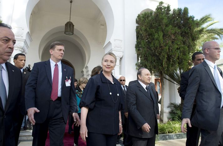 US Secretary of State Hillary Rodham Clinton, center, walks alongside Algerian President Abdelaziz Bouteflika, second right, following their meetings at Mouradia Palace in Algiers on Monday Oct. 29, 2012.  (AP Photo/Saul Loeb, Pool)