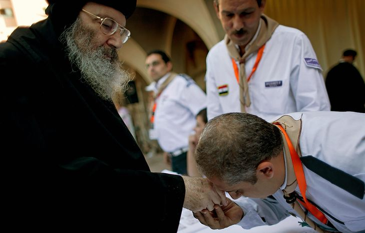 An election worker pays his respects to Coptic Bishop Bishoy, left, while he registers for voting during the new Coptic Pope elections at the main Coptic cathedral in Cairo, Egypt, Monday, Oct. 29, 2012. A council of Egypt's Coptic Christians is voting Monday in a process that will elect a new spiritual leader for the ancient church as the community struggles to assert its identity and role amid a rising tide of Islamism that has left many Copts fearful for their future. (AP Photo/Nasser Nasser)