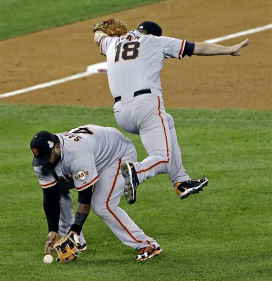 San Francisco Giants' Matt Cain (18) gets out of the way as Pablo Sandoval fields a bunt by Detroit Tigers' Quintin Berry during the third inning of Game 4 of baseball's World Series Sunday, Oct. 28, 2012, in Detroit. (AP Photo/Paul Sancya )