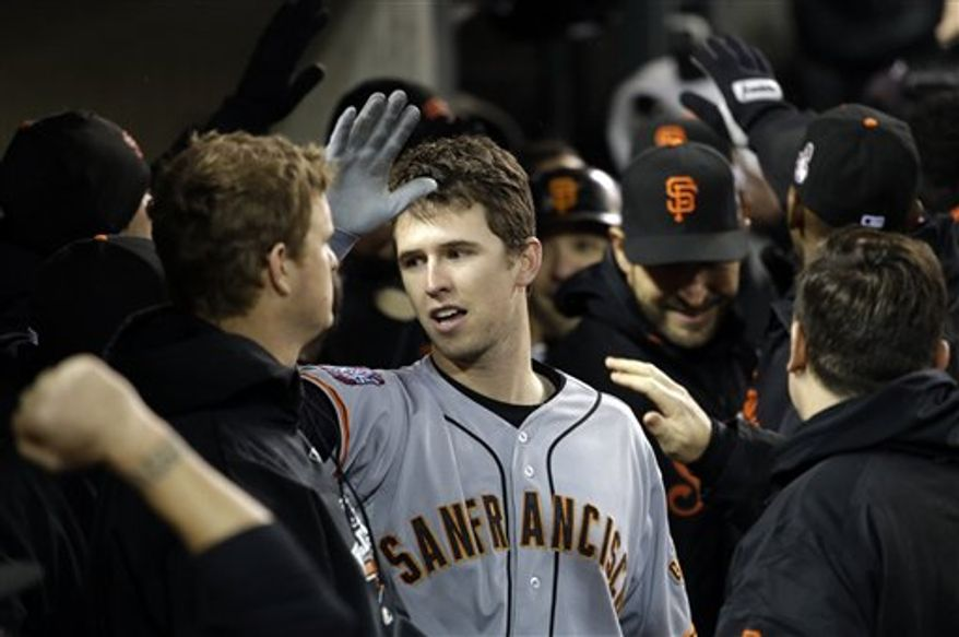San Francisco Giants' Buster Posey celebrates in the dugout after hitting a two-run home run during the sixth inning of Game 4 of baseball's World Series against the Detroit Tigers Sunday, Oct. 28, 2012, in Detroit. (AP Photo/David J. Phillip)
