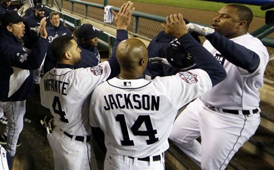 Detroit Tigers designated hitter Delmon Young, right, celebrates in the dugout after hitting a solo home run during the sixth inning of Game 4 of baseball's World Series Sunday, Oct. 28, 2012, in Detroit. (AP Photo/Matt Slocum)