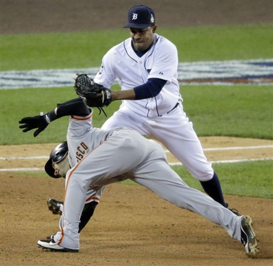 Detroit Tigers relief pitcher Octavio Dotel tags out San Francisco Giants second baseman Marco Scutaro as Giants third baseman Pablo Sandoval gets grounded out into a double play during the eighth inning of Game 4 of baseball's World Series Sunday, Oct. 28, 2012, in Detroit. (AP Photo/Charlie Riedel)