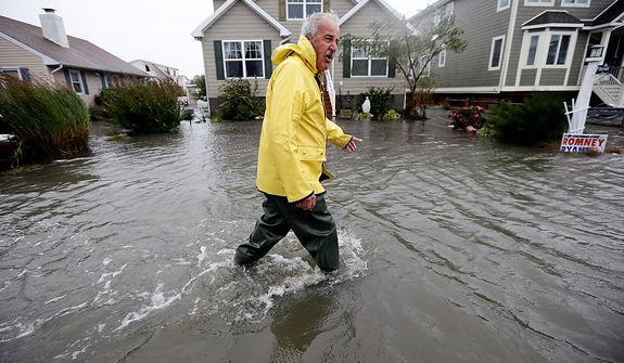 Richard Thomas walks through the floodwaters in front of his home after assisting neighbors as Hurricane Sandy bears down on the East Coast, on Monday, Oct. 29, 2012, in Fenwick Island, Del. Forecasters warned that the New York City region could face the worst of Sandy as it bore down on the Eastern Seaboard's largest cities Monday, forcing the shutdown of financial markets and mass transit, sending coastal residents fleeing and threatening high winds, rain and a wall of water up to 11 feet high. It could endanger up to 50 million people for days. (AP Photo/Alex Brandon)