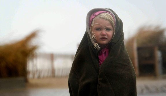 Matison Cos, 3, tries to stay warm and dry along the boardwalk as her family comes to see the approaching Hurricane Sandy in Rehoboth Beach, Del., on Sunday, Oct. 28, 2012. (AP Photo/The News Journal, Suchat Pederson)