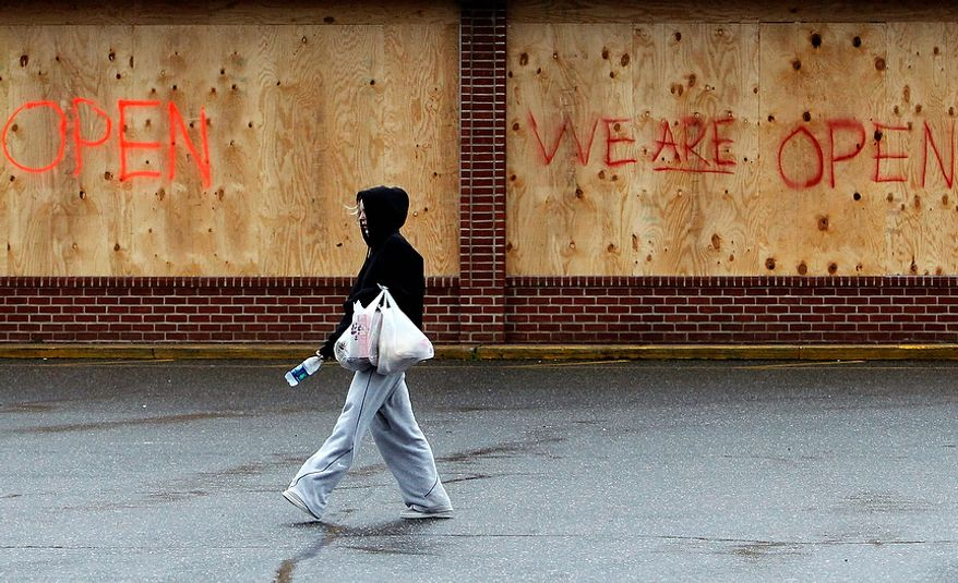 A woman carries bags back to her car after visiting a grocery store that is open for business despite being boarded up in advance of superstorm Sandy on Monday, Oct. 29, 2012, in Sayville, N.Y. Hurricane Sandy continued on its path Monday, forcing the shutdown of mass transit, schools and financial markets; sending coastal residents fleeing; and threatening a dangerous mix of high winds and soaking rain. (AP Photo/Jason DeCrow)