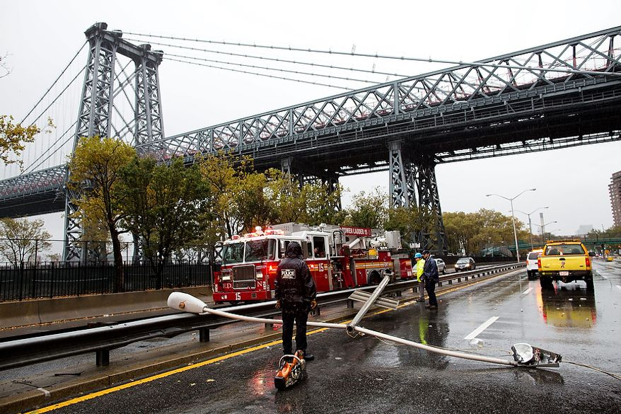 Police and firefighters respond to a downed street light on FDR Drive on Monday, Oct. 29, 2012, in New York. Hurricane Sandy continued on its path Monday, forcing the shutdown of mass transit, schools and financial markets; sending coastal residents fleeing; and threatening a dangerous mix of high winds and soaking rain. (AP Photo/John Minchillo)
