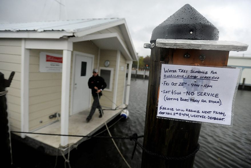 Brandon White of Watermark, a tour and charter boat company, ties one of the company's boats to a pier in Annapolis as Hurricane Sandy approaches the East Coast on Monday, Oct. 29, 2012. Hurricane Sandy continued on its path Monday, forcing the shutdown of mass transit, schools and financial markets; sending coastal residents fleeing; and threatening a dangerous mix of high winds and soaking rain. (AP Photo/Steve Ruark)