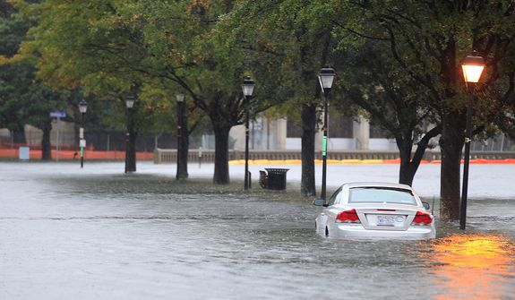 A stranded car sits along a street near downtown Norfolk, Va., on Monday, Oct. 29, 2012. Rain and wind from Hurricane Sandy were hitting the area. (AP Photo/Steve Helber)