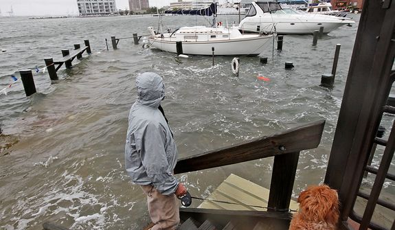 Jack Devnew and his dog check on his boat at a marina near downtown Norfolk, Va., on Monday, Oct. 29, 2012. Rain and wind from Hurricane Sandy were hitting the area. (AP Photo/Steve Helber)
