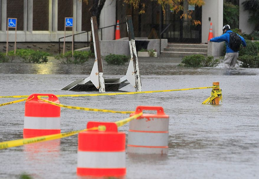 A Norfolk, Va., resident walks to work through floodwaters near downtown on Monday, Oct. 29, 2012. Rain and wind from Hurricane Sandy were hitting the area. (AP Photo/Steve Helber)