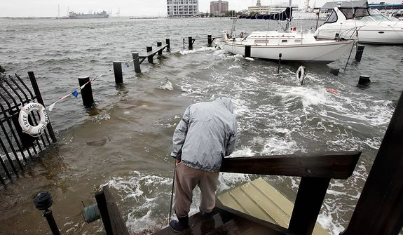 Norfolk, Va., resident Jack Devnew looks at the water covering a dock as he checks on his boat at a marina near downtown on Monday, Oct. 29, 2012. Rain and wind from Hurricane Sandy were hitting the area. (AP Photo/Steve Helber)