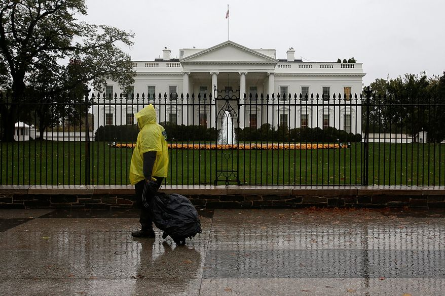 A lone man wearing a rain poncho walks past the White House in Washington on Monday, Oct. 29, 2012, during the approach of Hurricane Sandy. (AP Photo/Jacquelyn Martin)