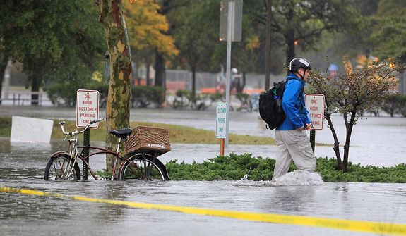 A Norfolk, Va., resident chains his bike and heads to work in floodwaters near downtown on Monday, Oct. 29, 2012. Rain and wind from Hurricane Sandy were hitting the area. (AP Photo/Steve Helber)